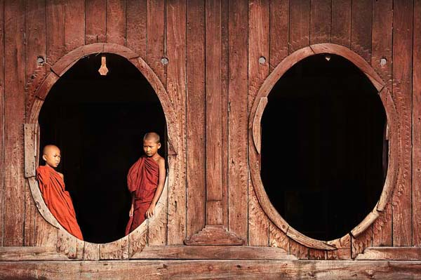 young monks at wooden doors